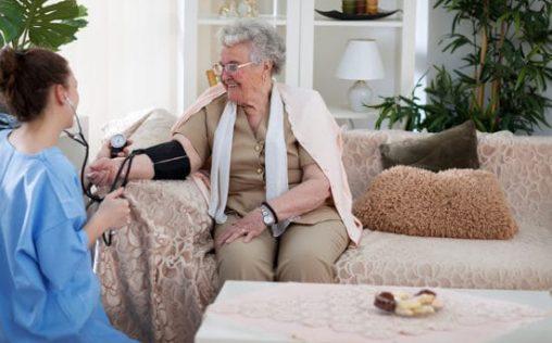 Nurse measuring blood pressure of smiling old woman