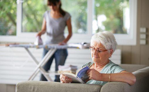 femme senior assise sur un canapé bouquinant près d'une femme