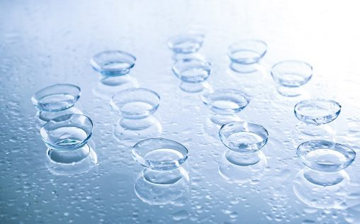 Contact lenses and drops of water on color background