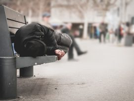 Poor homeless man or refugee sleeping on the wooden bench on the