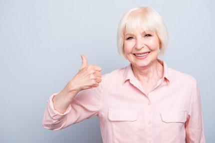 Old lady showing thumbs up gesture, smiling on grey background