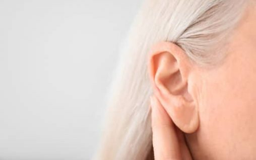 Mature woman with hearing problem on light background, closeup