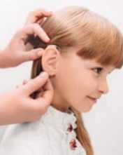 Doctor putting an hearing aid in a child's ear