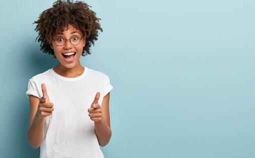 Joyous dark skinned woman points both fore fingers straightly at camera, wears casual clothing, happy to choose someone, isolated over blue background with empty space for your text or promotion