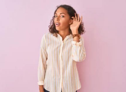 Young brazilian woman wearing striped shirt standing over isolated pink background smiling with hand over ear listening an hearing to rumor or gossip. Deafness concept.